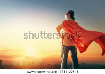Doctor wearing facemask and superhero cape during coronavirus outbreak. Virus and illness protection, quarantine. COVID-2019. Super hero power for  medicine. Person on sunset cityscape background. Royalty-Free Stock Photo #1711122841