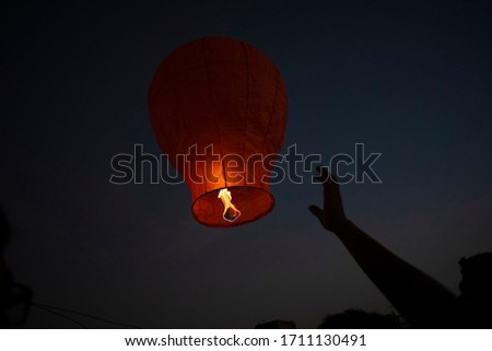 An Indian Bengali man celebrating Diwali by lighting flying lanterns in the sky in darkness. Indian lifestyle and Diwali celebration  #1711130491