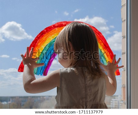 a happy little girl looks out the window with a painted rainbow. everything will be alright. a girl draws a rainbow on the window #1711137979