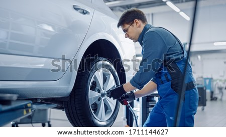 Mechanic in Blue Overalls is Unscrewing Lug Nuts with a Pneumatic Impact Wrench. Repairman Works in a Modern Clean Car Service. Specialists Removes the Wheel in Order to Fix a Component on a Vehicle. #1711144627