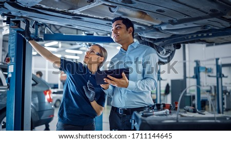 Female Mechanic Talking to a Manager Under a Vehicle in a Car Service. Specialist is Showing Info on a Tablet Computer. Empowering Woman Wearing Gloves and Safety Gloves. Modern Clean Workshop. #1711144645