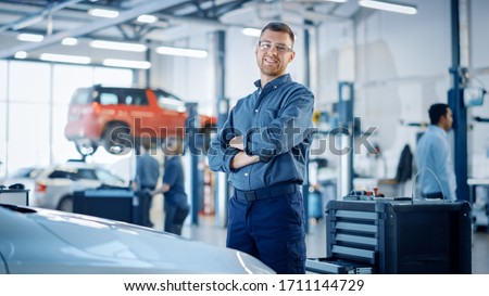 Handsome Car Mechanic is Posing in a Car Service. He Wears a Jeans Shirt and Safety Glasses. His Arms are Crossed. Specialist Looks at a Camera and Smiles. Royalty-Free Stock Photo #1711144729