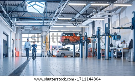 Female Mechanic Checks Diagnostics Results on a Tablet Computer and Explains a Vehicle Breakdown to a Manager. Car Service Employees Talk while Walking in a Garage. Modern Clean Workshop. Royalty-Free Stock Photo #1711144804