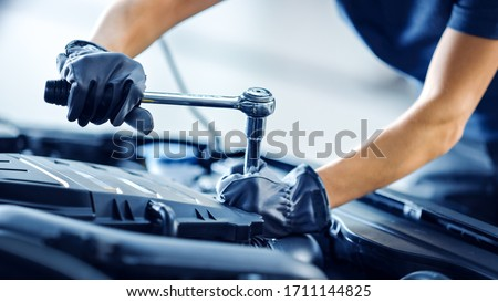 Close Up Shot of a Professional Mechanic Working on Vehicle in Car Service. Engine Specialist Fixing Motor. Repairman is Wearing Gloves and Using a Ratchet. Modern Clean Workshop. Royalty-Free Stock Photo #1711144825