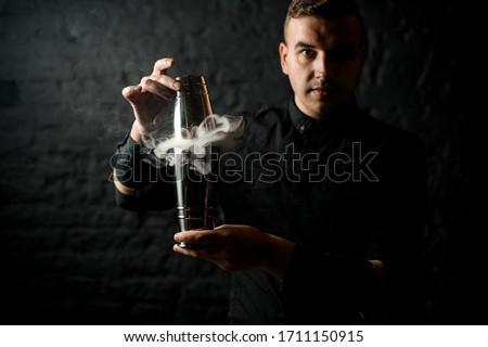 bartender in black shirt holds smoky steel shaker in his hands. Black brick wall in background. #1711150915