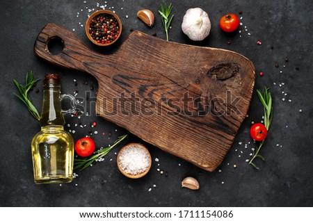 Cutting board and spices for cooking on a stone background Royalty-Free Stock Photo #1711154086