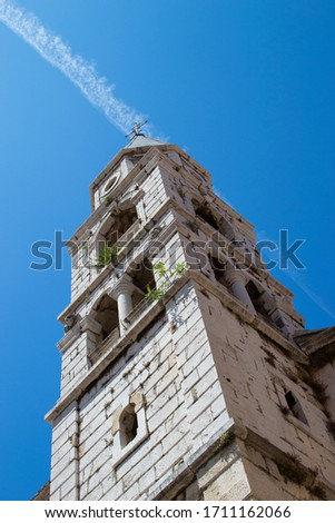 Vertical picture of the Bell Tower of St. Elias' Church (or Church of St. Elias) in the old town of Zadar, Croatia, with a vapur trail in the sky at the background