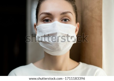 Close-up portrait of a girl in a protective medical mask near the window at home #1711183396