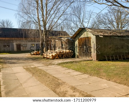 picture with a farm barn and prepared firewood for the winter, a simple household yard