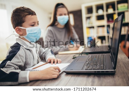 Boy and girl studies at home, wear protective masks, and doing school homework. Distance learning online education. #1711202674