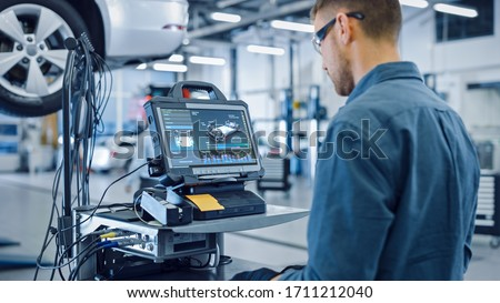 Car Service Manager or Mechanic is Running an Interactive Diagnostics Software on an Advanced Computer. Specialist Inspecting the Vehicle in Order to Find Broken Components and Errors in Data Logs. Royalty-Free Stock Photo #1711212040