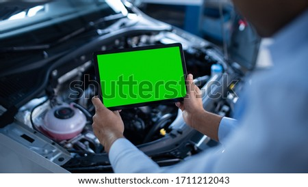 Car Service Manager or Mechanic Uses a Tablet Computer with a Green Screen Mock Up that is Pointed at an Enginer Bay. Specialist Inspecting the Vehicle in Order to Find Broken Components In the Engine