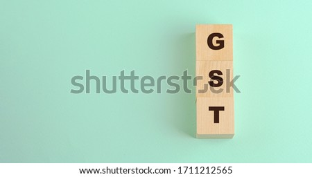 abbreviation gst inscription on wooden blocks isolated on blue background investment finance concept #1711212565