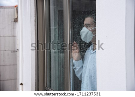 Man with mask, looking through the window. Man in quarantine for coronavirus. #1711237531
