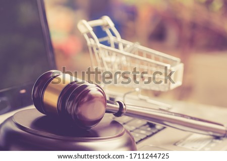 E-commerce law, rules and regulations concept : Wooden judge gavel and shopping cart on a laptop, depicts good practice vendor must do for consumer e.g provide clear data, order cancellation, refund #1711244725