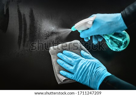Surface cleaning disinfecting home with sanitizing antibacterial wipes protection against COVID-19 spreading wearing medical blue gloves. Sanitize surfaces prevention in hospitals and public spaces. Royalty-Free Stock Photo #1711247209