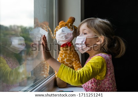 Child stay at home with toy. Little girl looking outdoors. Corona virus prevention.