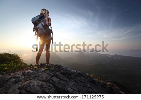 Young lady hiker standing with backpack on top of a mountain and enjoying sunrise #171125975
