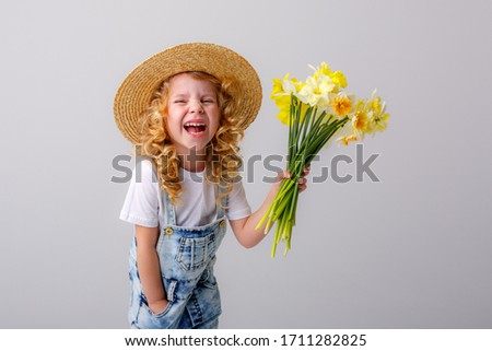 portrait of a little blonde girl holding a bouquet of spring flowers in a straw hat on a white background