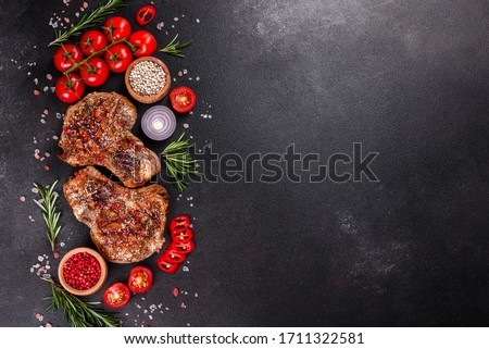Fresh delicious juicy steak on the bones with vegetables and spices against a dark background. Pork juicy steak grill on dark table Royalty-Free Stock Photo #1711322581