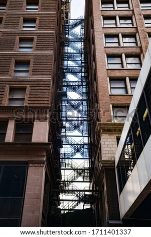 A long flight of fire escape staircase packed between two old buildings downtown. Reminiscent of Peter Parker in a New York City alleyway or West Side Story.