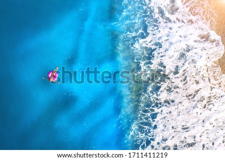 Aerial view of a young woman swimming with the donut swim ring in the clear blue sea with waves at sunset in summer. Tropical landscape with girl, azure water, sandy beach. View from above. Travel #1711411219
