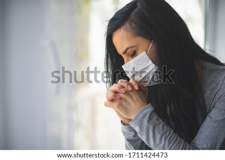 Portrait of woman with surgical mask praying next to window #1711424473