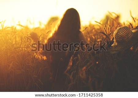 golden sunset. A wheat field and a girl going forward, she holds her favorite hat in her hands. Image with selective focus  #1711425358