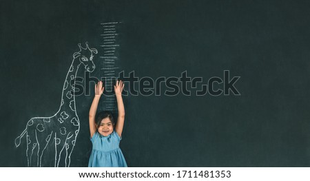 A girl measures her height against a dark Board with a picture of a giraffe