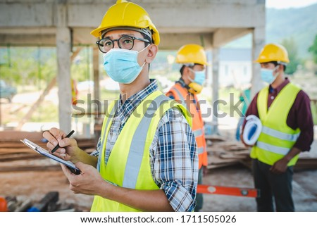 A team of construction engineers and three architects are ready to wear medical masks. Corona or Covid-19 wear masks during the design of construction. #1711505026