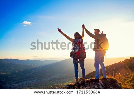 happy couple man and woman tourist at top of mountain at sunset outdoors during a hike in summer #1711530664