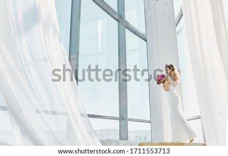 Fashion bride in gorgeous wedding dress. Beautiful model with bridal makeup and hairstyle in marriage dress. With a bouquet of flowers in hand #1711553713