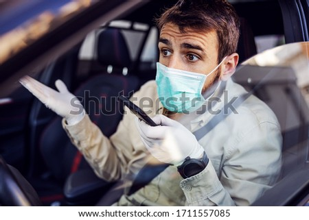 Man with protective mask and gloves driving a car talking on mobile phone smartphone. Infection prevention and control of epidemic. World pandemic. Stay safe. #1711557085