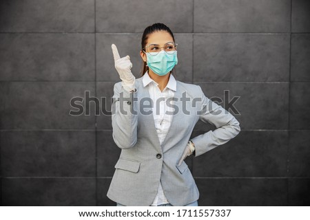 Young woman in business suit with mask and gloves, prevent infection of Covid-19 virus coronavirus,contamination of germs or bacteria. Infection prevention and control of epidemic.  #1711557337