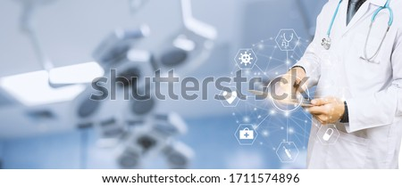 Banner close up of healthcare and medical doctor using smart tablet device for research development on coronavirus and diagnosis on patient health concept, surgeon scrub and stethoscope in hospital   Royalty-Free Stock Photo #1711574896