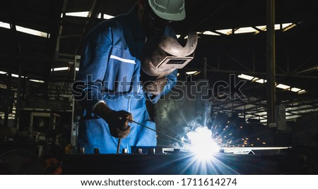 Industrial worker welding metal with many sharp sparks #1711614274