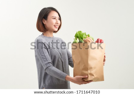 Young woman with a grocery shopping bag. Isolated on white background. #1711647010