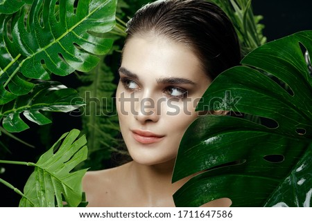 Pretty woman hid in the green leaves of a palm tree #1711647586