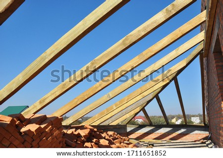 A close-up on framing the rooftop of a brick house with trusses, roof beams, roof eaves, braces and planks in roofing construction.  #1711651852