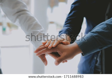 businessman joining united hand, business team touching hands together after complete a deal in meeting. unity teamwork partnership corporate concept. #1711688983