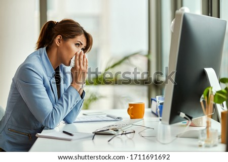 Young entrepreneur sneezing in a tissue while working at her office desk.  #1711691692
