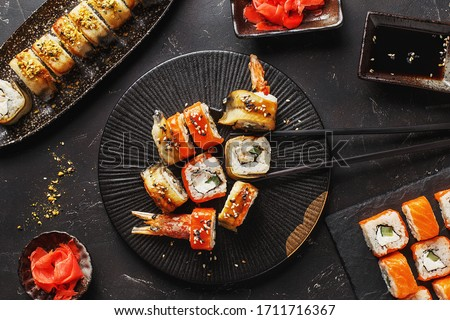 Set of various sushi rolls with soy sauce, ginger and chopsticks over dark concrete background. Philadelphia roll, roll with with eel and cream cheese, roll with with langoustine, salmon and eel #1711716367