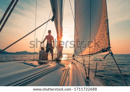 Young couple sailing on the boat at sunset Royalty-Free Stock Photo #1711722688