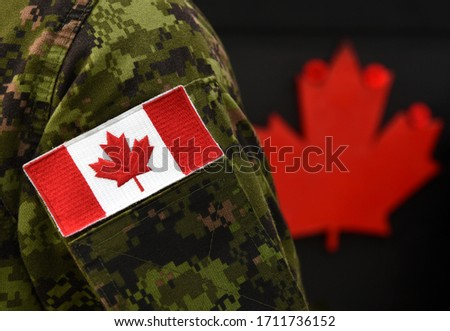 Canada Day. Flag of Canada on the military uniform and red Maple leaf on the background. Canadian soldiers. Army of Canada. Canada leaf. Remembrance Day. Poppy day.  #1711736152