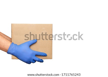 Hand in blue medical glove gives cardboard box.?oncept of safety mail goods courier delivery in virus or coronavirus quarantine. Donation concept. Voluntary assistance to those in need.Volunteering #1711765243