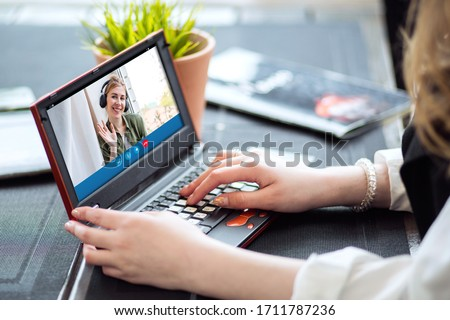 A happy blonde woman using a laptop computer to video call friends and parents, a girl sitting at home on the window #1711787236