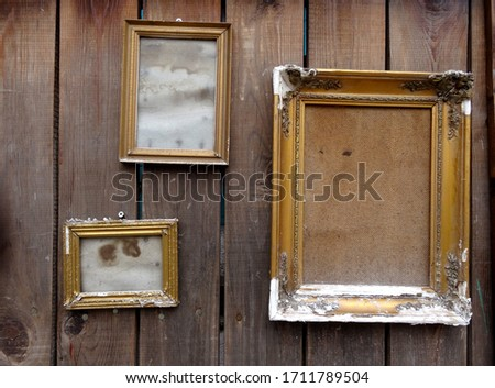 Old, empty picture frames on a rustic wooden wall.