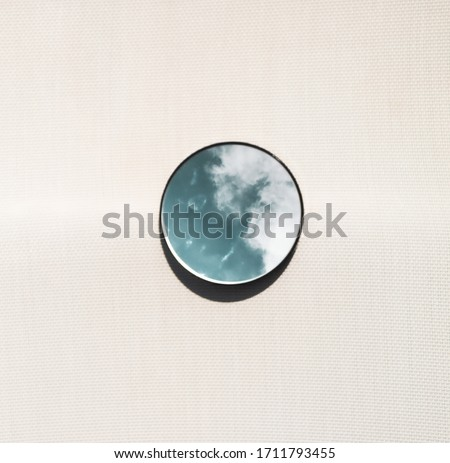 Elegant and artistic image of a mini circular mirror with reflections of the blue sky with clouds on a light and bright brown background