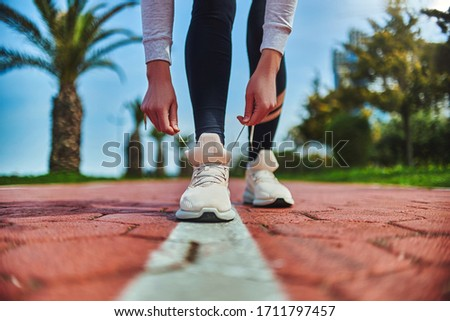 Fitness woman ties shoelaces on beige sneakers and get ready for morning jogging and sports workout outdoors. Do sport and be fit. Sports people with healthy sporty lifestyle     Royalty-Free Stock Photo #1711797457