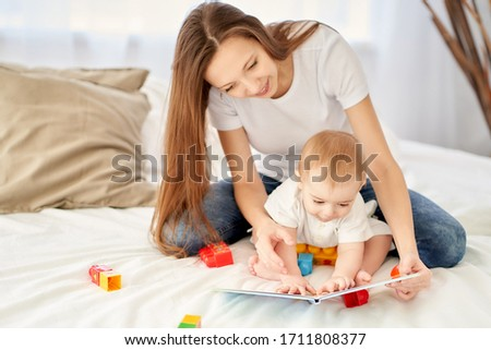 A young, beautiful mother with long hair sitting on the bed with her baby shows him pictures in a book.
